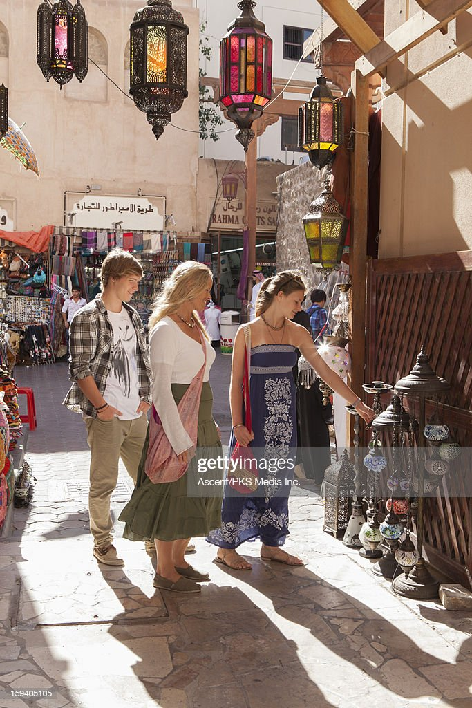 Family of 3 shop for lamps in old souk market : Stock Photo