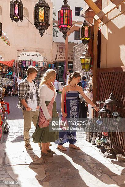 Family of 3 shop for lamps in old souk market