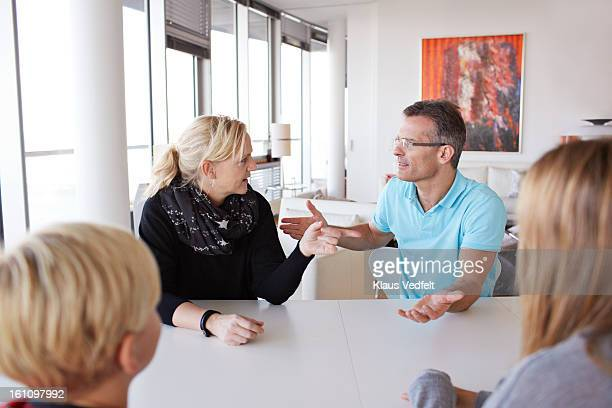Family of 4 having a discussion at dinner table