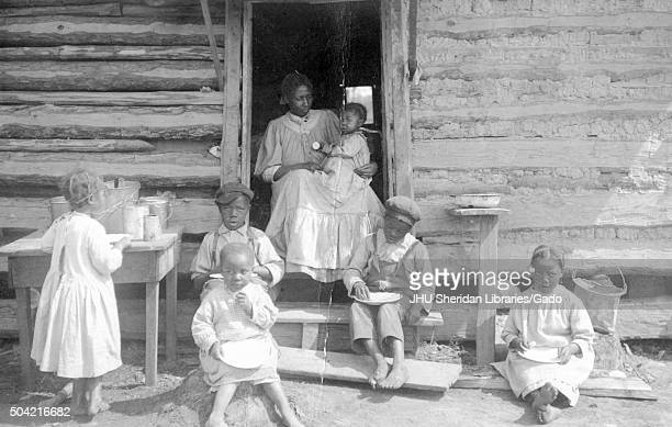 Family of africanamerican sharecroppers the mother sitting in the door of a log cabin and holding young baby several other children sitting and...