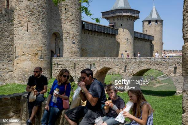 A family of children and parents eat lunch in front of medieval towers on 27th May in Carcasonne LanguedocRousillon south of France Situated on the...