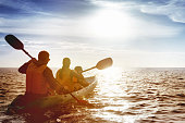 Kayaking concept with family of father mother and son swimming at sea at sunset time. Space for text