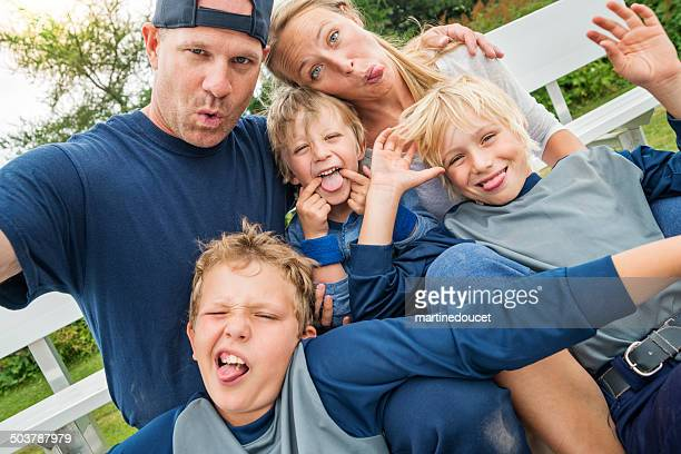 Family of five making faces for selfie after baseball game.