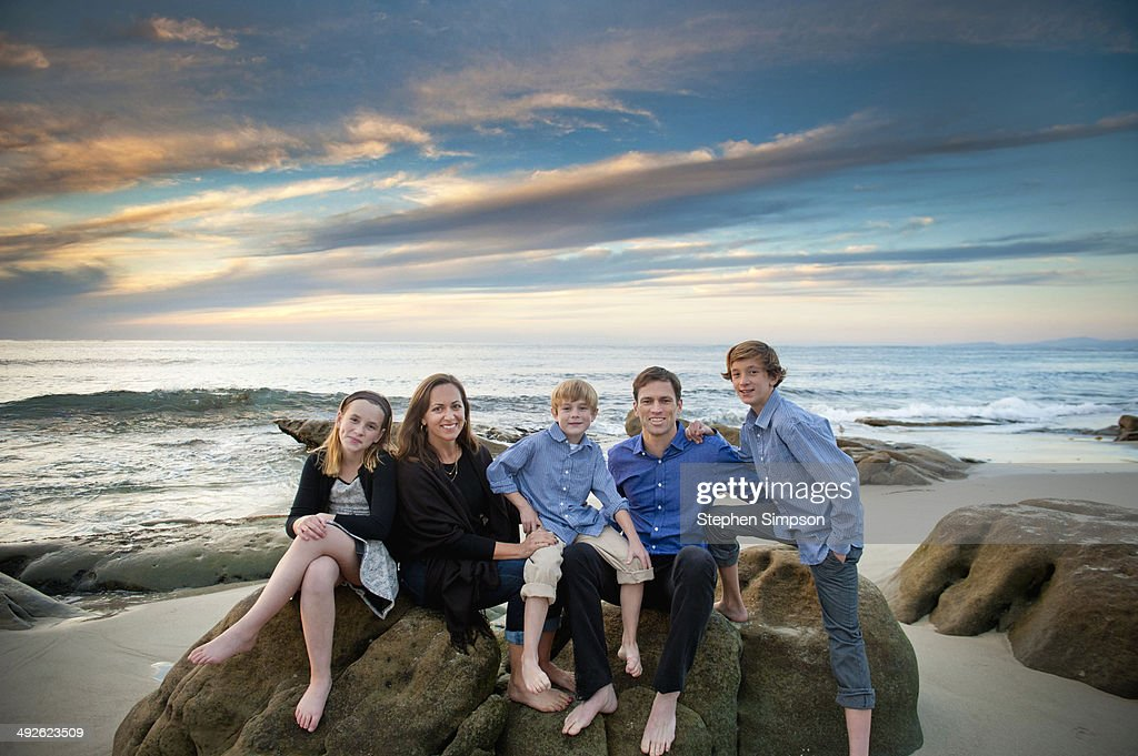 family of five posing on seaside boulders : Stock Photo