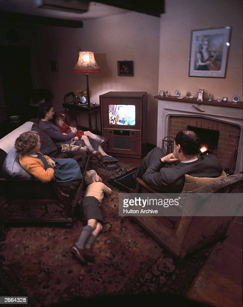 A family of five relax in front of their colour television