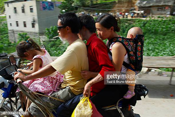 Family of five riding on motorcycle, side view