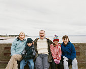 Family of Five Sit on a Wooden Bench By the Sea Having
