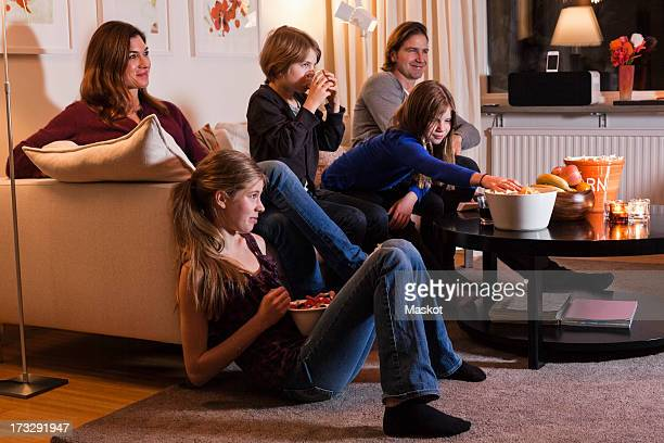 Family of five watching television together in living room