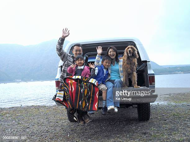 Family of four and dog on tailgate of car, smiling, portrait
