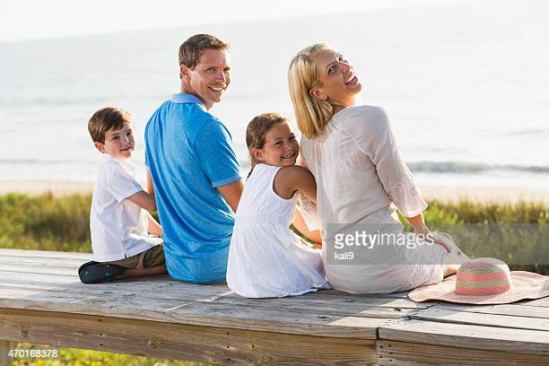 Family of four at beach on a bench overlooking water