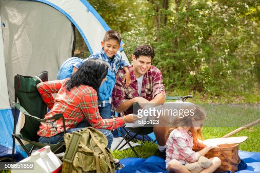Family of four camping outdoors in forest. Tent, supplies. : Stock Photo