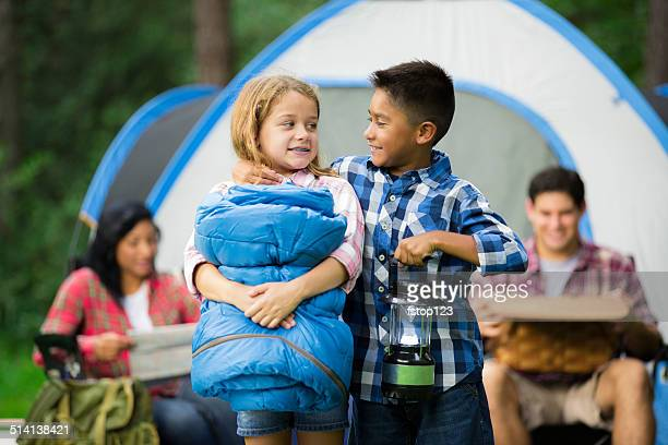 Family of four camping outdoors in forest. Tent, supplies.