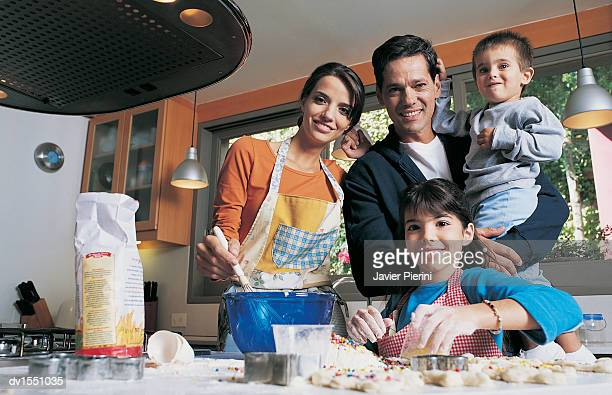 Family of Four Cutting Pastry in a Kitchen Together