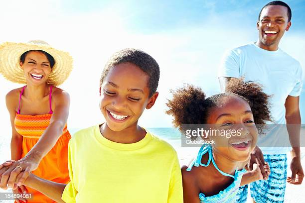 Family of four enjoying summer vacation in the beach