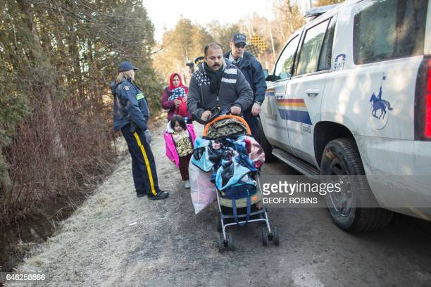 A family of four from Pakistan is led away by RCMP officers after they illegally crossed the USCanada border near Hemmingford Quebec February 28 2017...