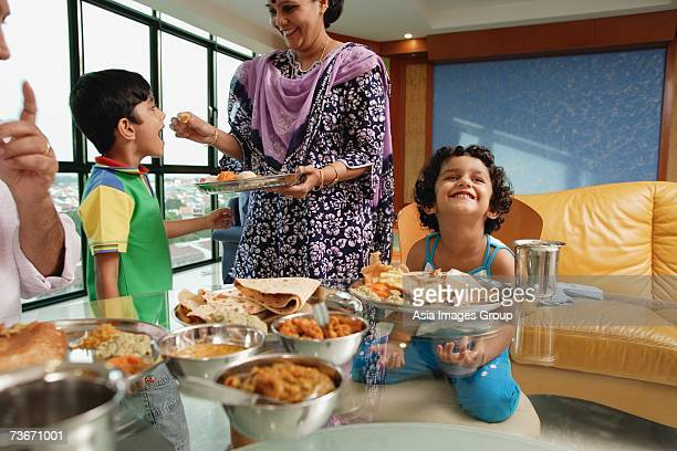 Family of four having a meal at home, mother feeding son