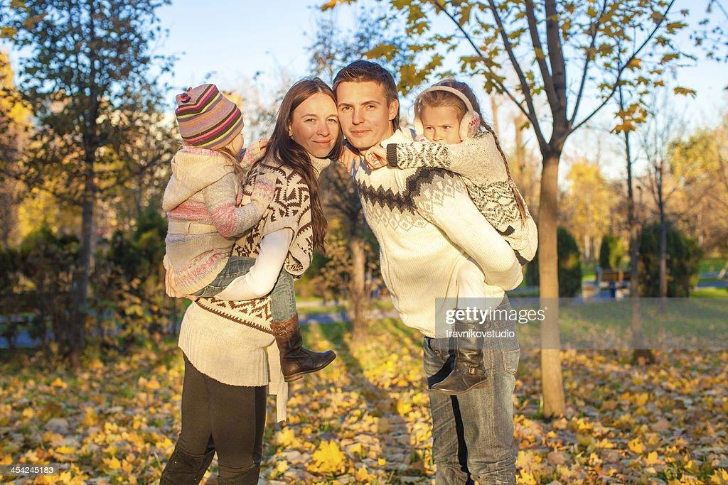 Family of four having fun in autumn park : Stock Photo