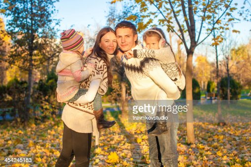 Family of four having fun in autumn park : Stock Photo
