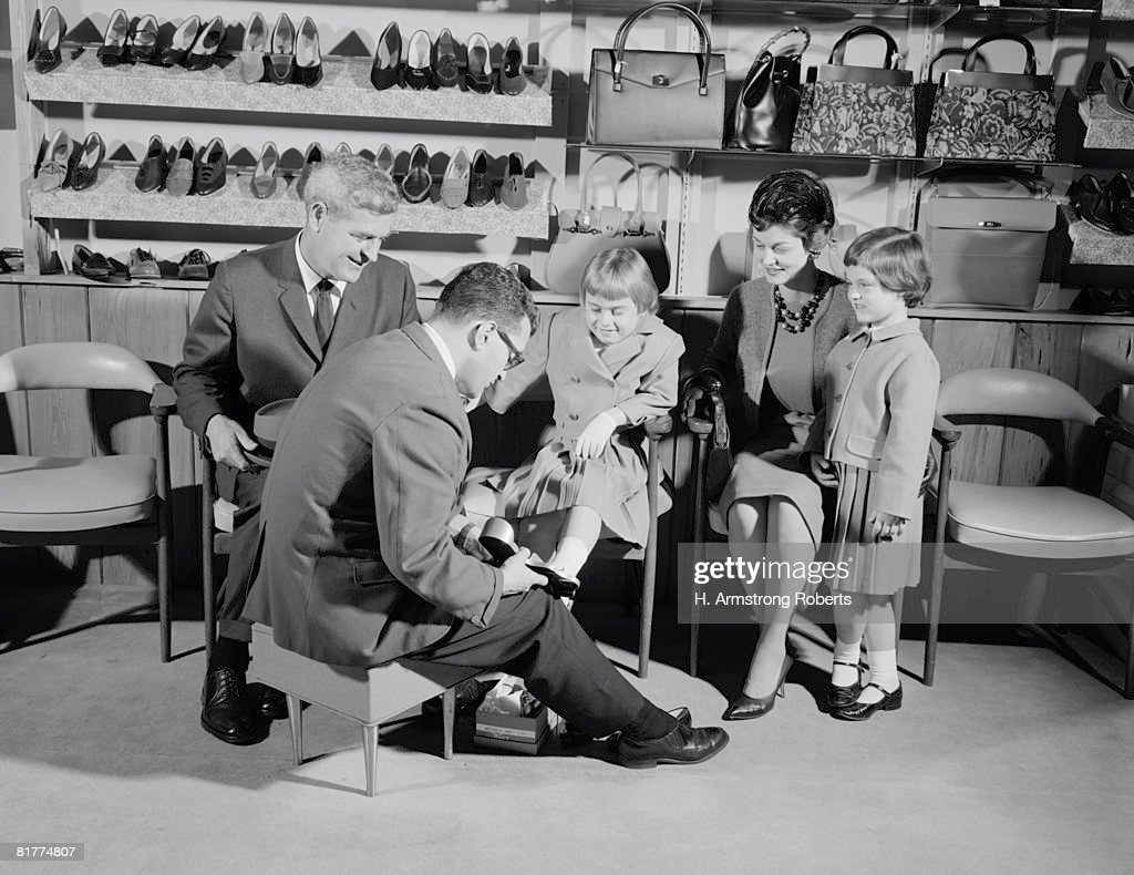Family of four in shoe shop, salesman fitting shoe on girl as mother, father and sister look on. : Stock Photo