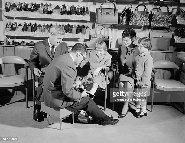 Family of four in shoe shop, salesman fitting shoe on girl as mother, father and sister look on.