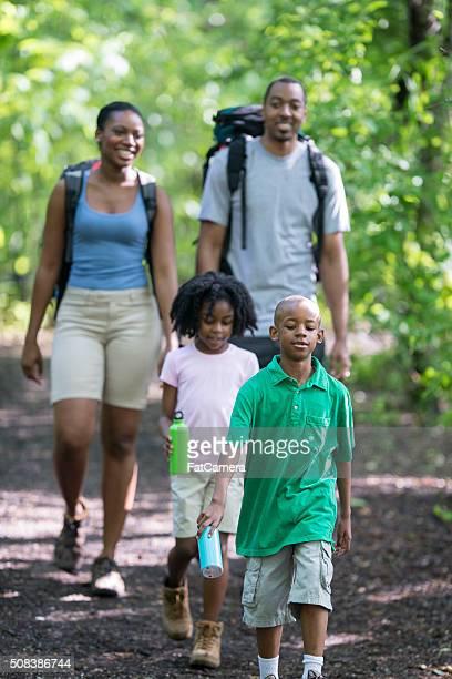 Famille de quatre personnes est de la randonnée dans les bois