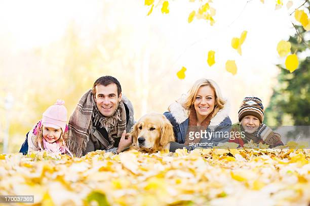 Family of four people with their dog in park.