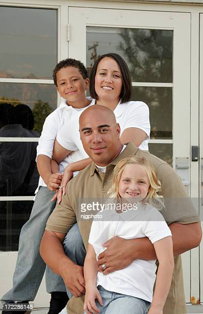 Family of four posing in front of house