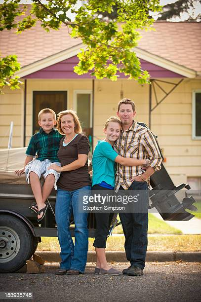 family of four posing in front of their house