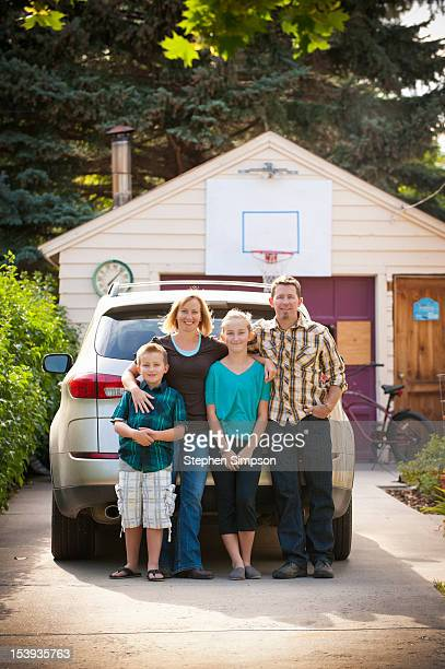 family of four posing in the driveway