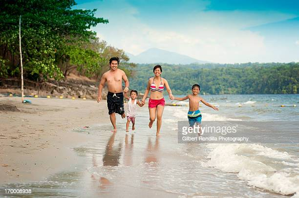 Family of four running on the beach