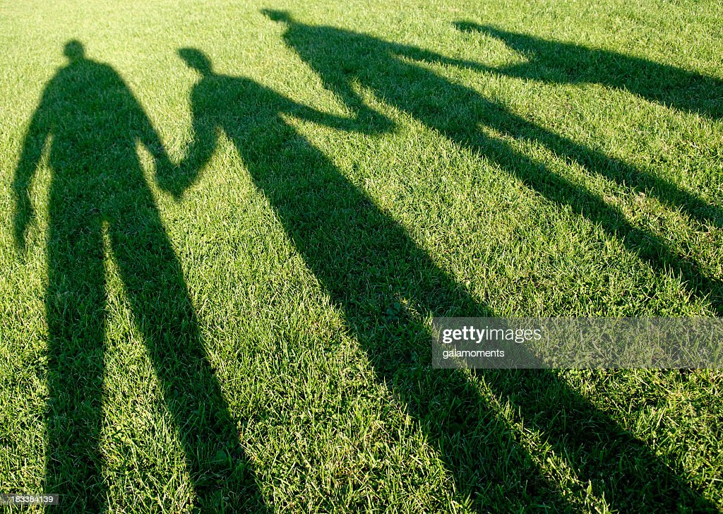 Family of four shadows in the park