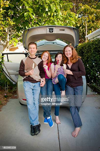 family of four sharing popsicles on car trunk