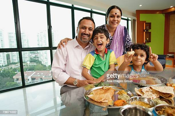 Family of four sitting around dining table, smiling at camera