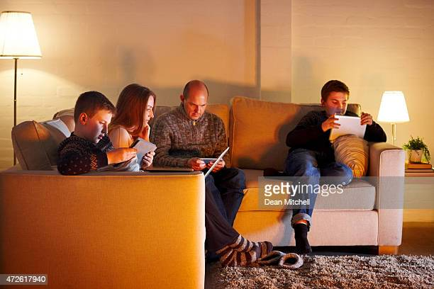 Family of four sitting on couch using digital devices