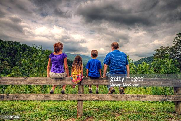 Family of four sitting on fence