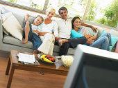 Family of four sitting on sofa, smiling, portrait