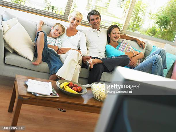 Family of four sitting on sofa, smiling, portrait
