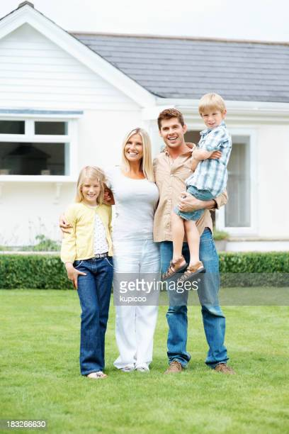 Family of four standing on lawn at home