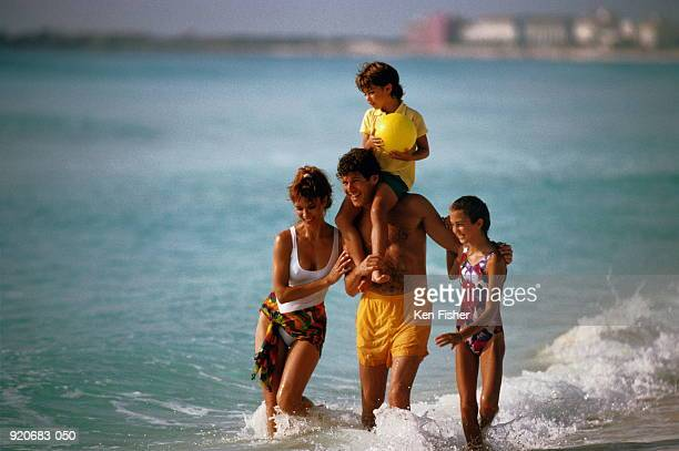 Family of four walking along beach, boy(6-8)on father's shoulders