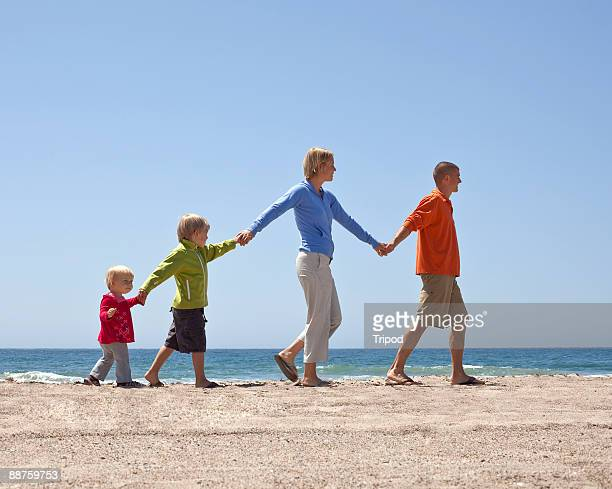 Family of four walking hand and hand on beach