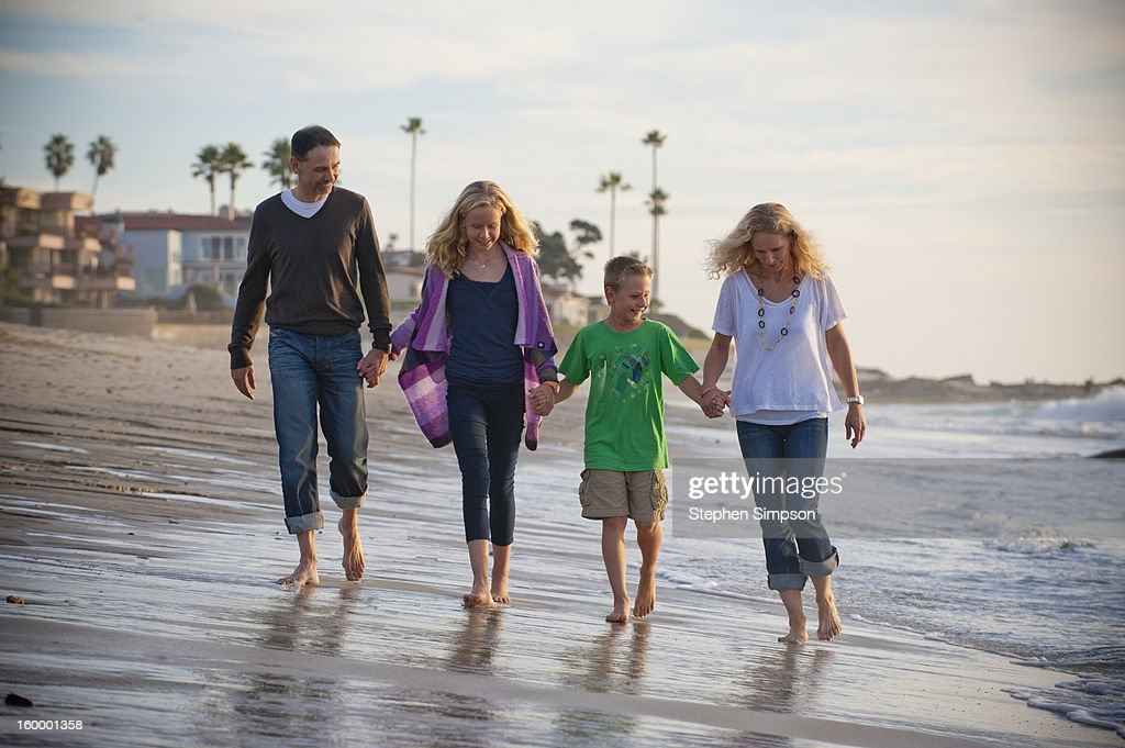family of four walking on the beach : Stock Photo
