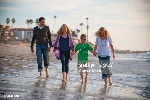 family of four walking on the beach : Stock Photo