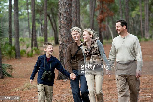 Family of four walking together in park