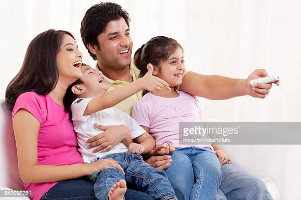 Family of four watching television