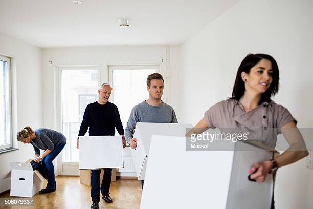 Family of four with cardboard boxes moving into new house