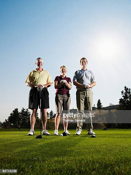 Family of golfers standing on tee, smiling