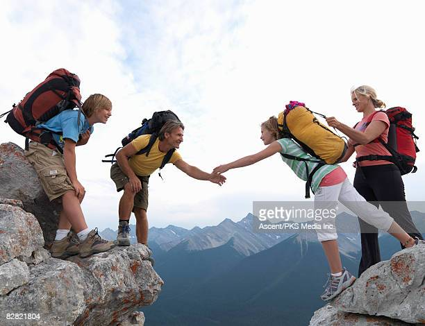 Family of hikers helping each other over rock gap,