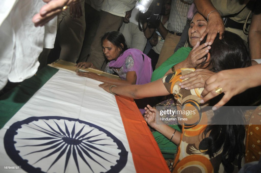 Family of Indian prisoner Sarabjit Singh mourning over his coffin covered in Indian National Flag at his native house in Bikhiwind on May 2, 2013 about 40 Kms from Amritsar, India. Sarabjit Singh, an Indian prisoner in Pakistan died after being brutally assaulted in a Pakistani jail. Meanwhile, a second autopsy was conducted on Thursday night by a team of six doctors at the government-run Amritsar Medical College to ascertain the cause of Sarabjit's death. The first postmortem was carried out at the Jinnah Hospital in Lahore.