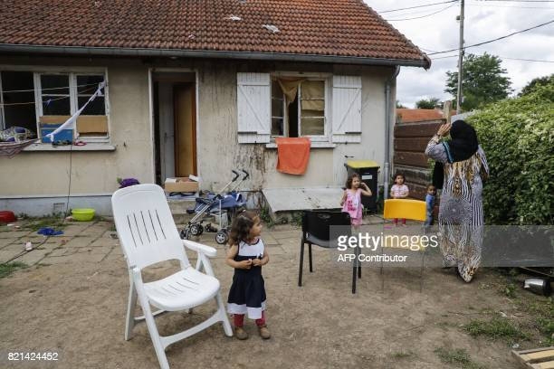A family of migrants threatened of eviction are pictured on July 20 2017 outside a house they live in since 2015 at the former Cite de l'Air housing...