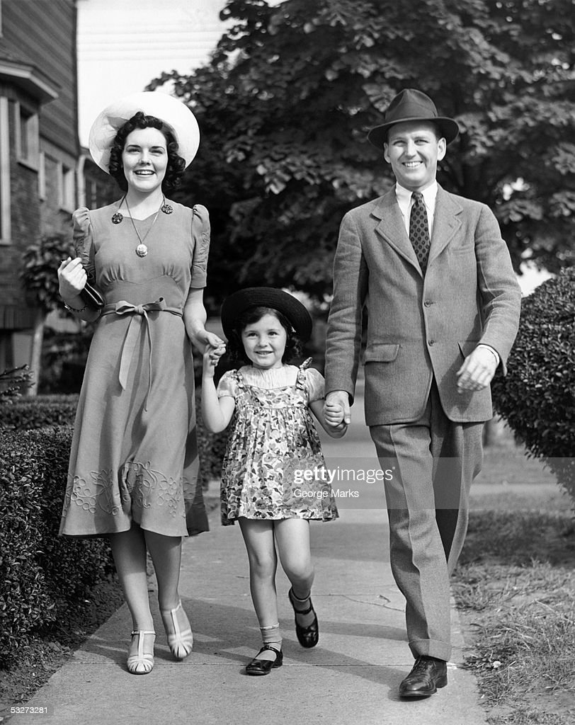 Family of mother father and daughter walking on street : Photo